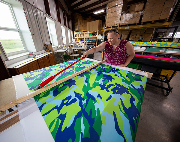 Deb Techmeier cuts custom fabric to make a designer laundry bag for a summer camper. She sewed the bag at another production station.