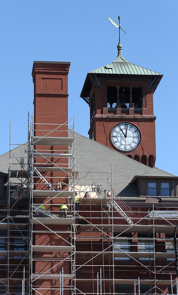 Workers on scaffolding repair the south side of Bowman Hall.