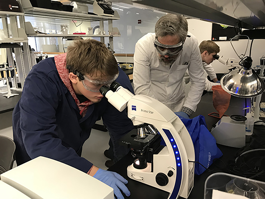 Mykiah Young looks for red and white bloods through a microscope at UW-Stout, as Colfax High School science teacher Mark Mosey looks on.