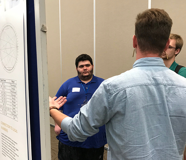 James Evans, left, talks with other student researchers from the McNair Scholars Program.
