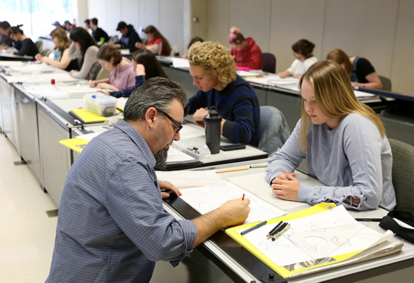 Instructor Joshua Wilichowski talks with a student in the Design Drawing and Concept Visualization class at UW-Stout.