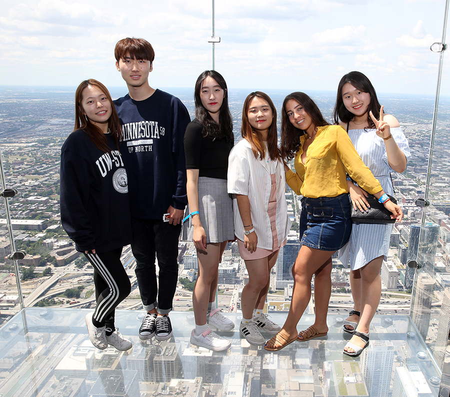 A group of students attending UW-Stout this summer stand on the observation ledge atop Willis Tower, formerly Sears Tower, during a university-guided trip to Chicago.