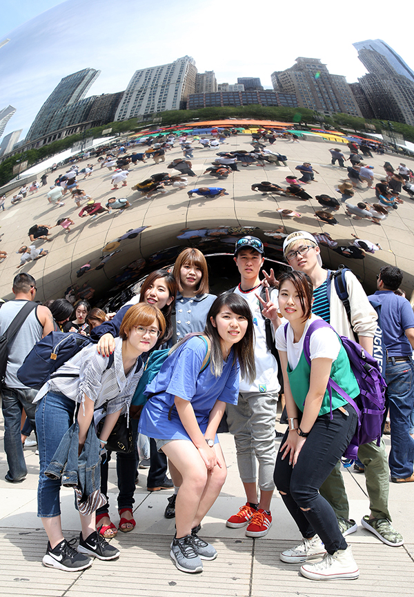 International students at UW-Stout huddle under the Cloud Gate sculpture in Chicago's Millennium Park. The Michigan Avenue skyline is reflected above them.