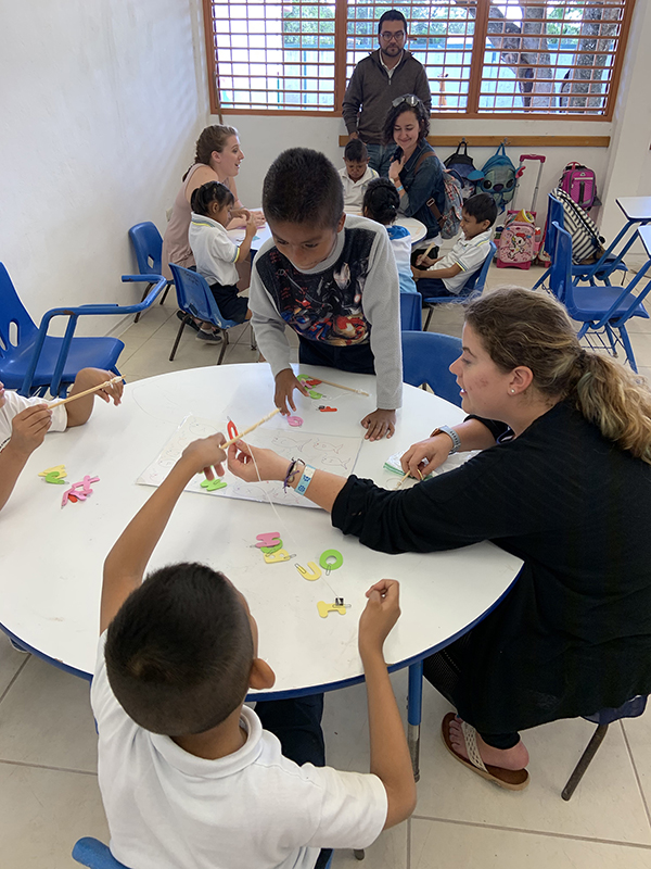 UW-Stout students Heidi Fliehs, front table, and back table Amayssia Wahljohnson, left, and Kristen Pease help children in a Cozumel, Mexico, school with activities.