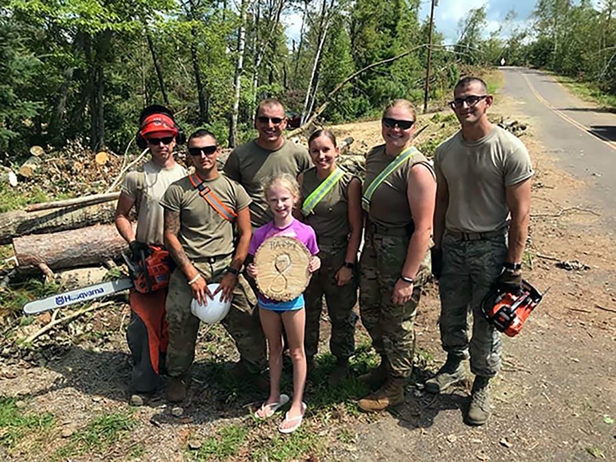 ​​​​​​​Alysha Stieber, third from right, and other Wisconsin National Guard members present a girl with a birthday memento made from a fallen tree while on duty this summer near Loon Lake in Barron County.