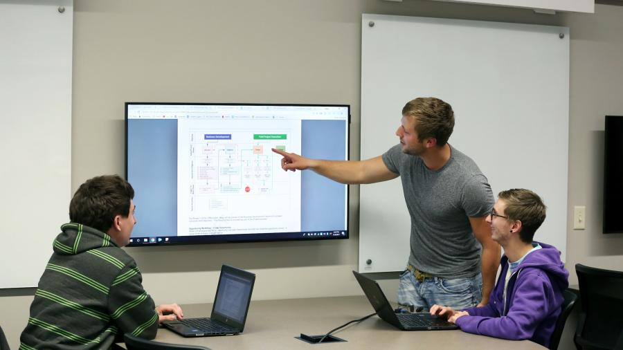 Students work on group tasks during Senior Lecturer Evan Sveum's Information Technology Policy and Audit class.