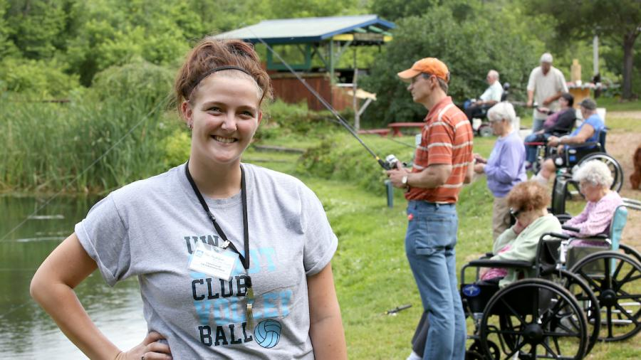 HDFS student Chelsea Lavold is a life enhancement intern with The Neighbors of Dunn County, a new model of non-institutional nursing homes in Menomonie, WI. Lavold is photographed working with residents during a fishing outing at Bullfrog Fish Farm.