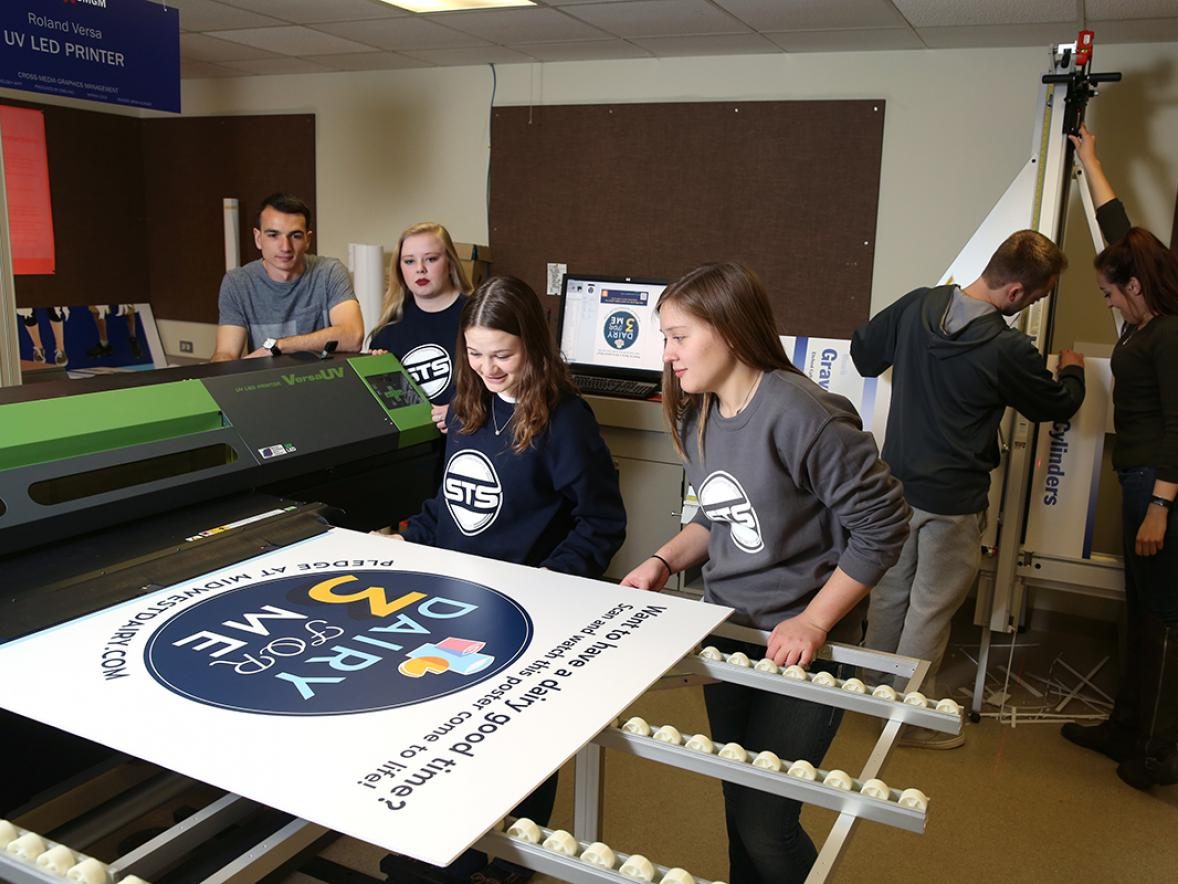 Graphic communications students work in a printing lab.