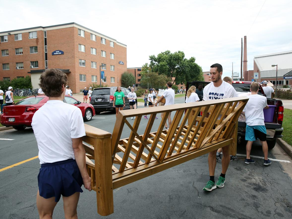 Athletes help a new student move a futon frame into a residence hall in 2018.
