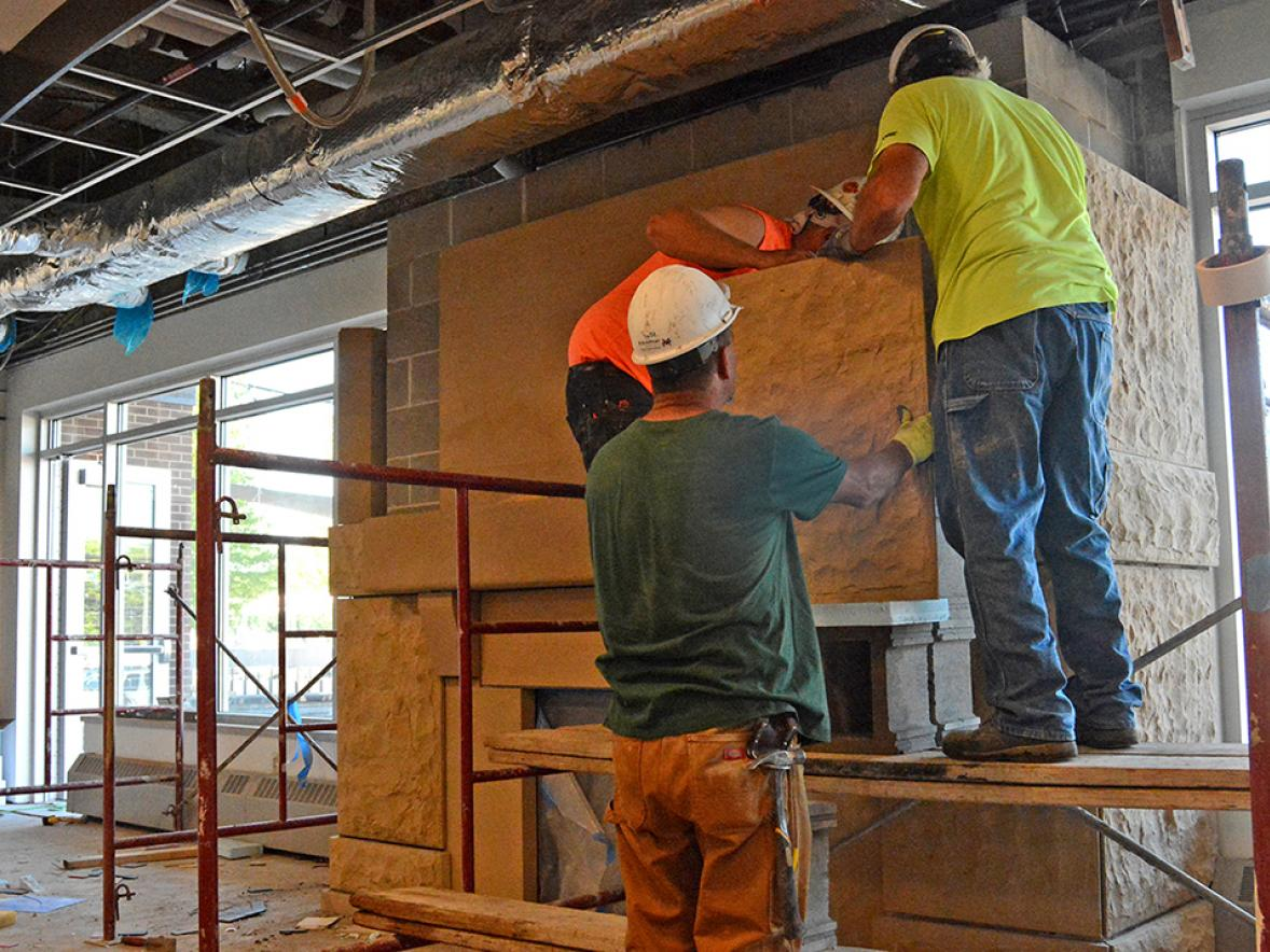 Workers with R.J. Jurowski of Whitehall lift pieces of Dunnville sandstone into place for the new fireplace in UW-Stout's Merle M. Price Commons. / UW-Stout photo by Don Steffen