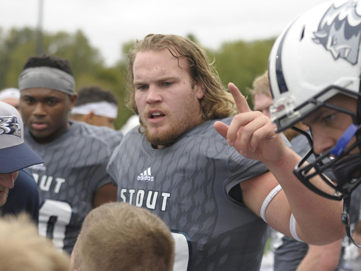 Aaron Wisecup, a semifinalist for a national student athlete award, talks with teammates during a 2018 UW-Stout football game.