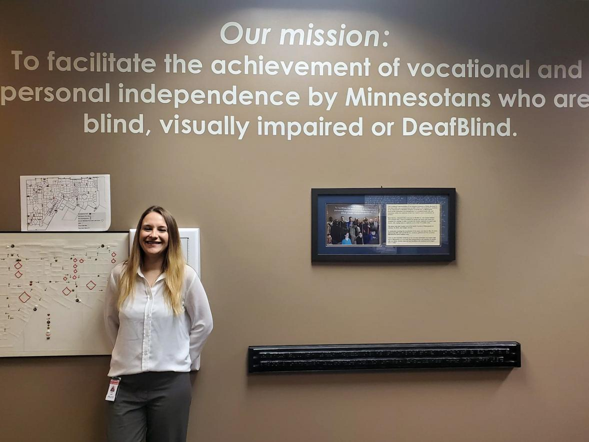 Alumna Natasha Jerde is director of Minnesota State Services for the Blind. She stands next to the agency's mission statement.