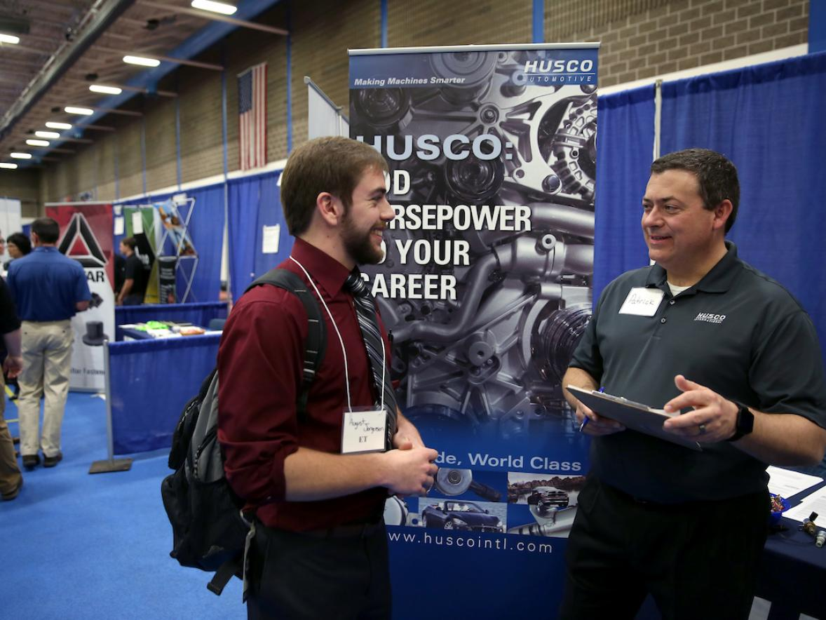 Pictured is engineering technology student August Jorgensen speaking with a representative at the Husco Automotive booth.