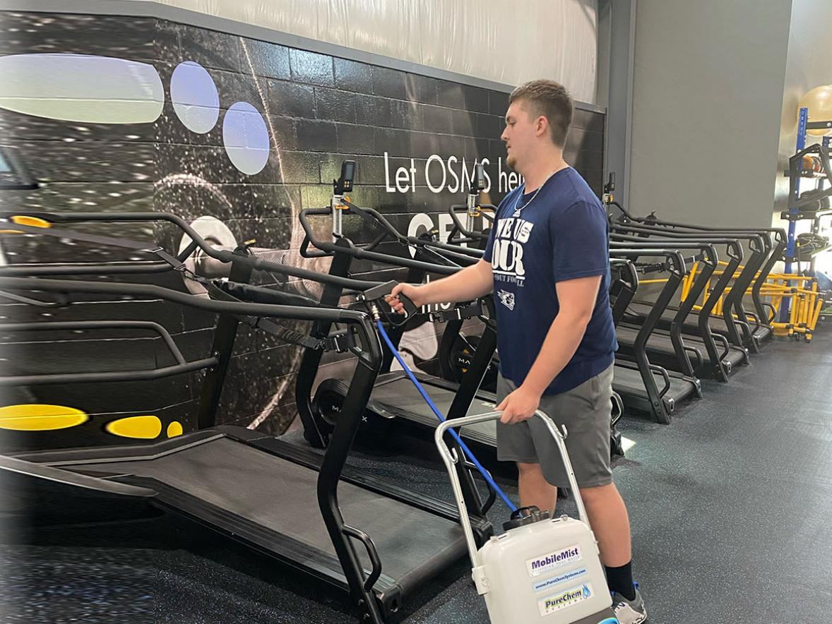 UW-Stout student Matt Rotter disinfects gym equipment at Synergy Sports Performance in Hobart using a MobileMist. Over the summer Rotter did a Cooperative Education and Internship Program at a Green Bay company that has products designed to curb the spread of COVID-19.