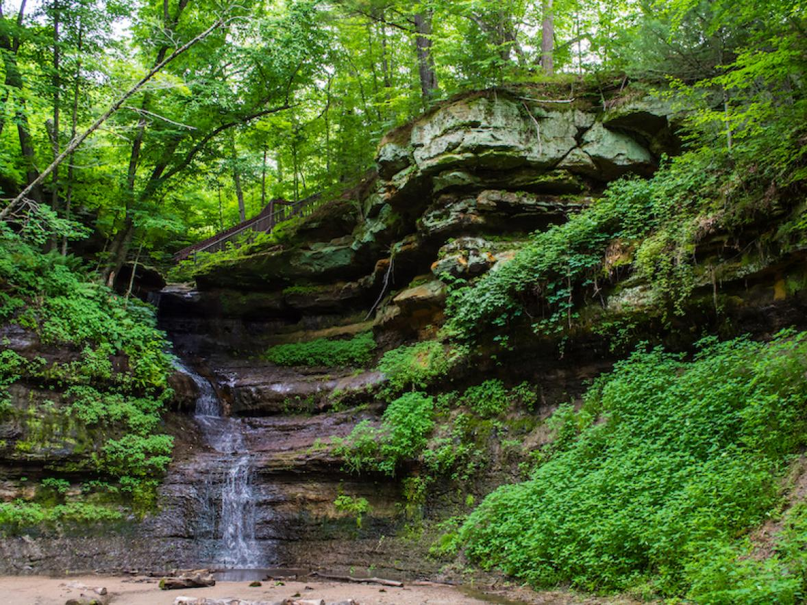 Devils Punchbowl shows off lush green foliage and a waterfall.