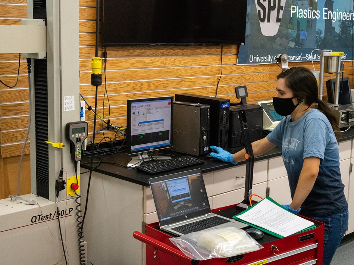 A lab assistant in the UW-Stout Plastics Lab sets up an experiment for students who take readings remotely and use a virtual meetings program to communicate.