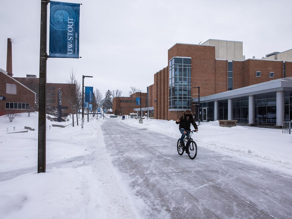 A bicyclist rides across campus in freshly fallen snow. / UW-Stout photo