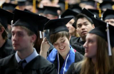 A UW-Stout graduate smiles while awaiting her diploma at Commencement.