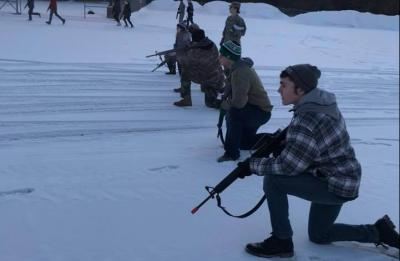 ROTC studens bounding in snowy parking lot.