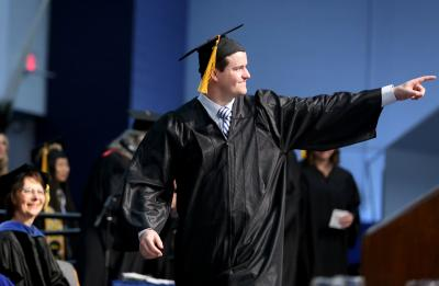 Nick Super celebrates during his walk across the Johnson Fieldhouse stage to receive his diploma.