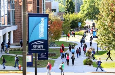 Students walking outside in Spring between Jarvis Hall and the MSC with a Stout flag in the foreground.