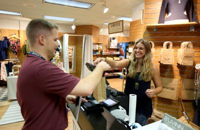 A UW-Stout student helps a customer at the Niche, a campus store run by retail merchandising and management majors.
