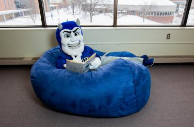 UW-Stout's mascot Blaze the Blue Devil reading in the library.