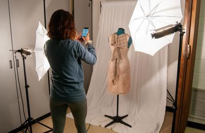 A student photographs her work in a fashion and retail lab.
