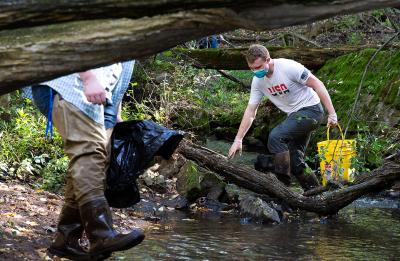 Chris Jones, right, president of the Natural Areas Club, pulls items from the creek.