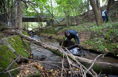 Assistant Professor Keith Gilland removes part of a couch from the creek.